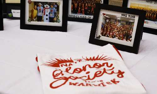 National Honor Society t-shirt on table with photos.