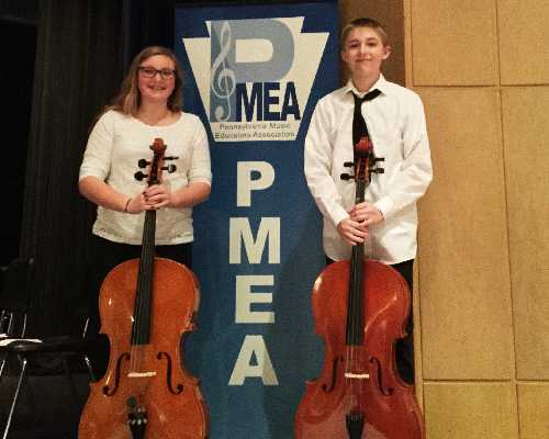 students pose for photo with string instruments